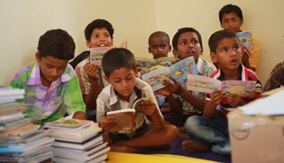 Village children reading the books in the Library