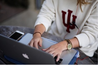 Indiana University uses Salesforce for recruiting, admissions, marketing, communications, graduate schools and HR case management. Image of student with computer.