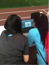 Salesforce employee volunteer get hands on with Wave Analytlcs activity and local middle school girl.