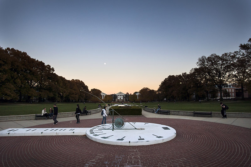Sundial at dusk, with students walking by.