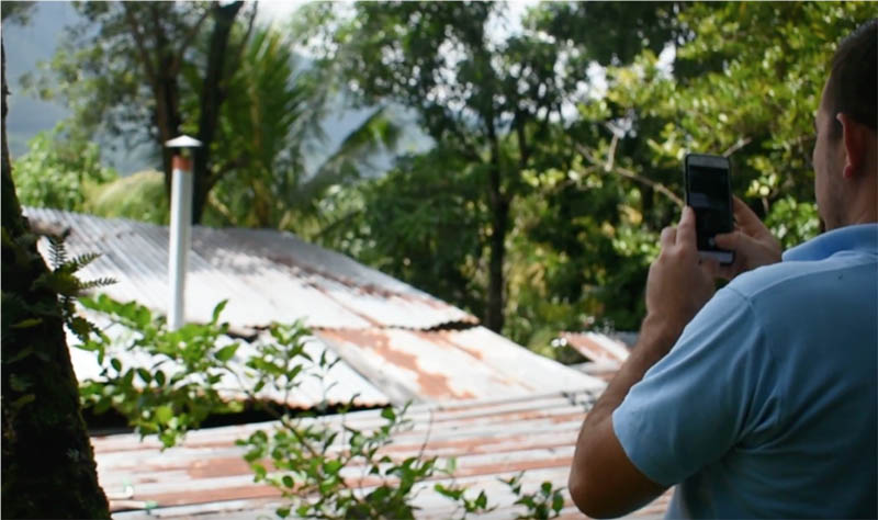 A nonprofit employee takes a photo of cookstove installation to get feedback in near-real-time