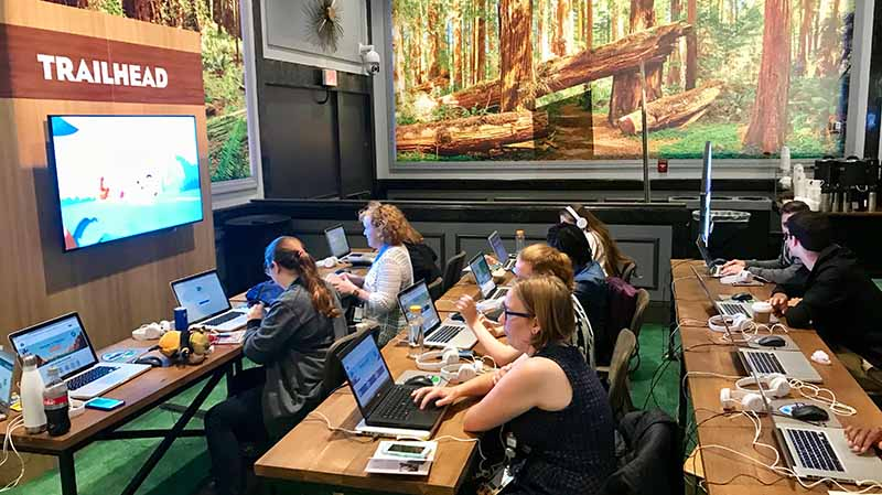 Learning is more fun when you do it in the community! Photo of Dreamforce attendees working on Trailhead trails together.