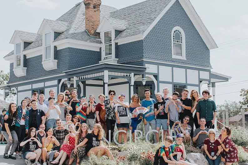 LGBTQ+ youth posing for a picture in front of Encircle house
