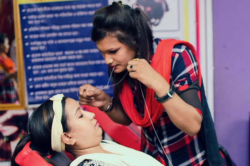 BRAC program participant Shabnoor learning a trade hands-on with a customer in a beauty salon.