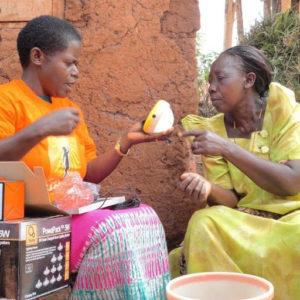 Solar Sister entrepreneur demonstrates a solar lamp. Source: Solar Sister