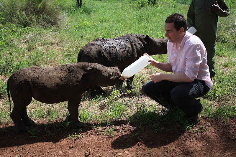 Thijs volunteers in Kenya, feeding a baby rhino