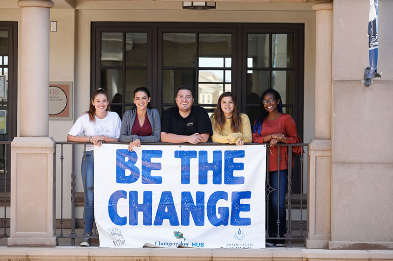 "University of San Diego students with a banner saying ""Be The Change."""