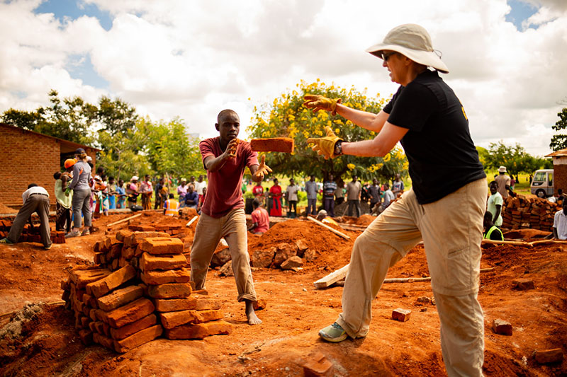 Karen Mettling, Spirit Aerosystems software engineer and volunteer, passing bricks on a worksite