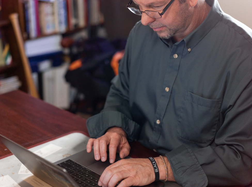 A higher education leader at his computer