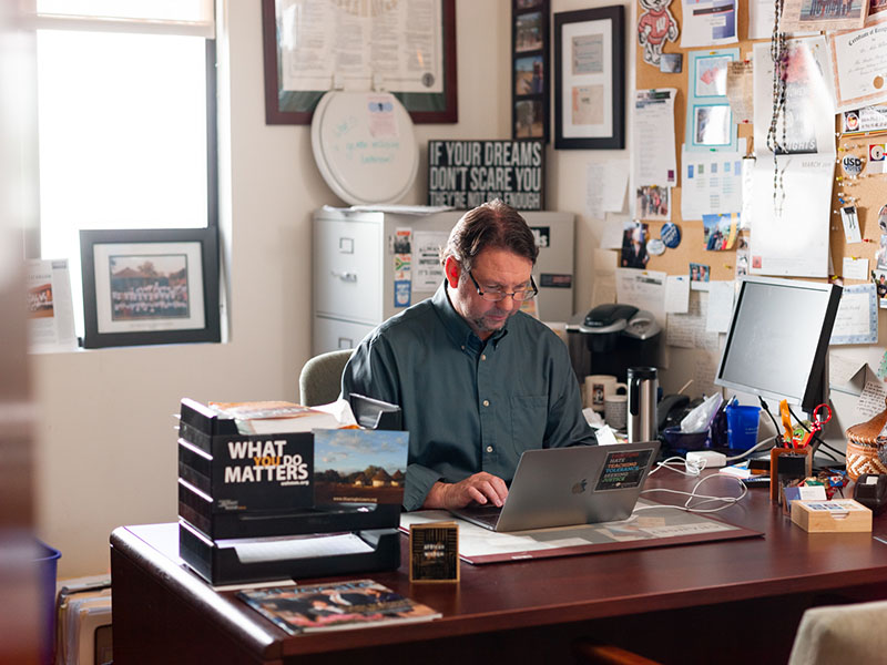 A higher ed staff member at the University of San Diego at his desk.