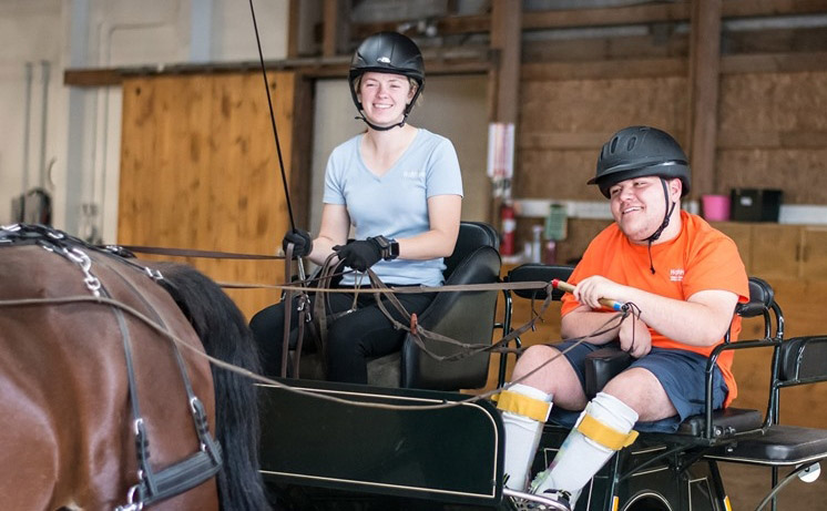 High Hopes participant, Mac, with Advanced Instructor, Sarah Miller, during a therapeutic carriage driving lesson.