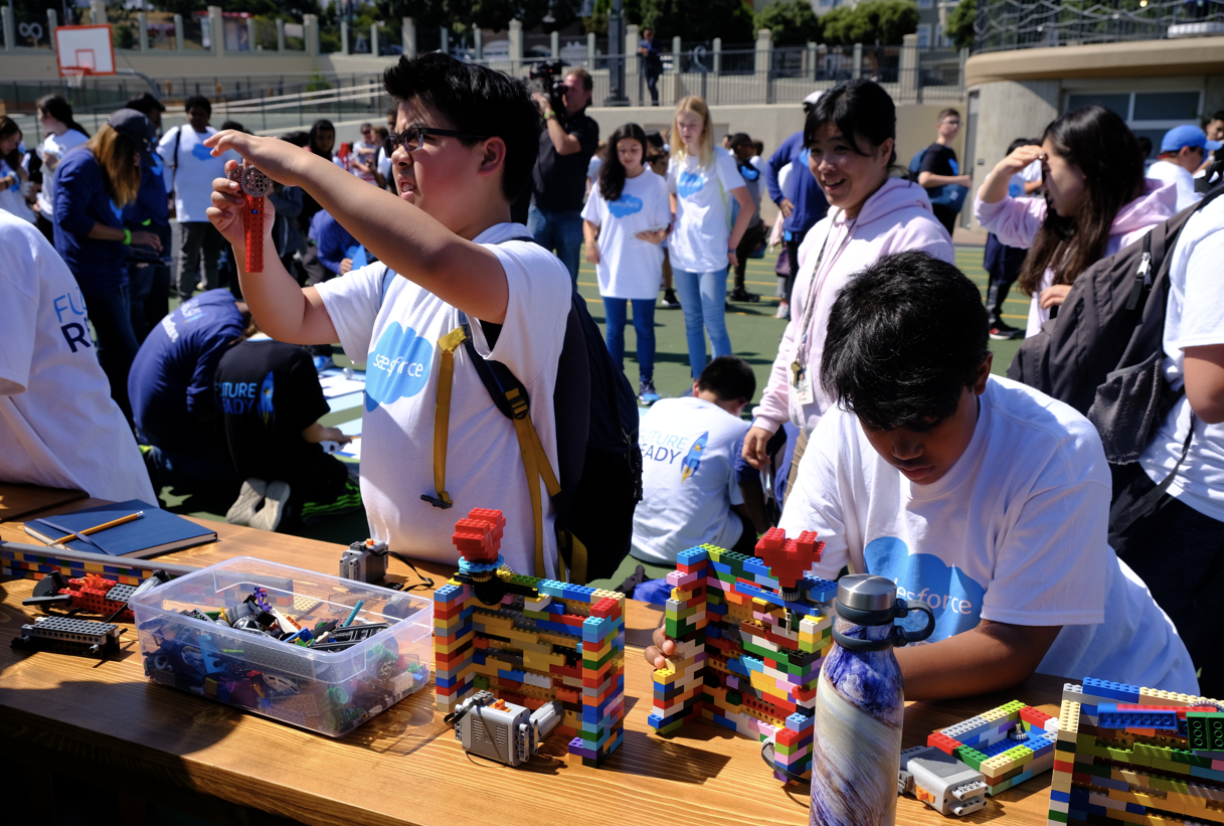 Students at a Salesforce volunteer event using LEGOs powered by electronics to learn engineering skills. Choosing a platform is similar to having the right building blocks to create what you want, as well as options to create things out of the box.