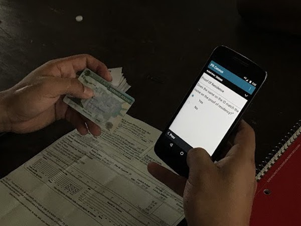 GiveDirectly field officer enters information from an ID into the TaroWorks app.