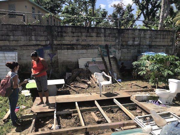 A GiveDirectly field officer assesses damage of an applicant's home in Puerto Rico during a house visit.