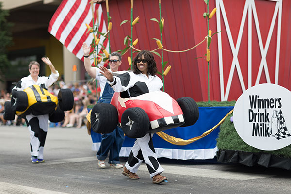 People with race car outfits walking along a float with a giant cow, promoting milk drinking, at the Indy 500 Parade.