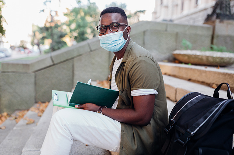 Male student sitting on a staircase in front of a university, taking notes in his note book and studying, while wearing a mask.