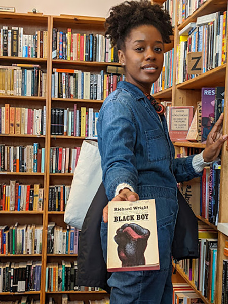 Author Katie Mitchell shows a book written by a black author, in the bookstore she owns with her mother - Good Books.