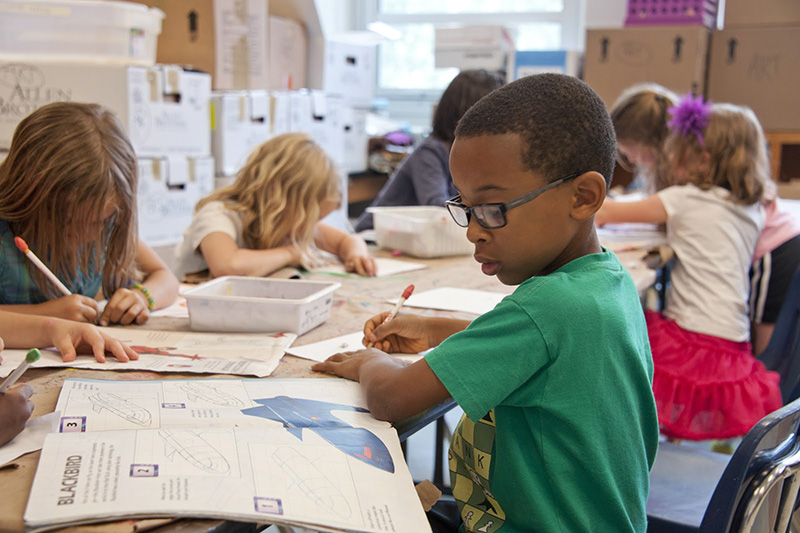Kids learning to draw in a classroom.