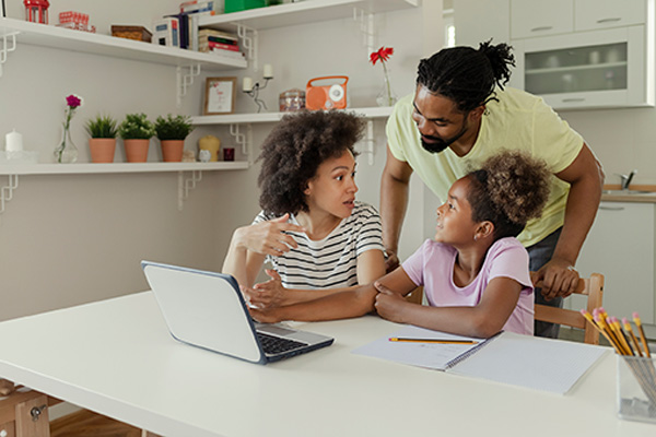 Parents helping daughter with remote learning