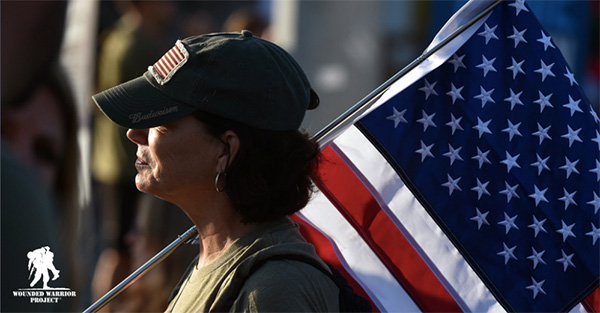 Woman carrying the American flag, with Wounded Warrior Project logo