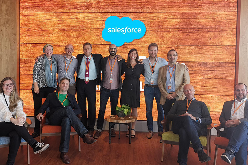 Group of men and women in front of Salesforce logo