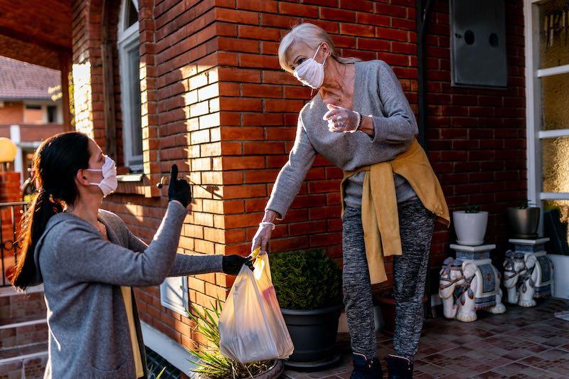 Volunteer bringing groceries to an older woman at home