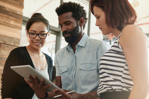 Three people looking at ipad