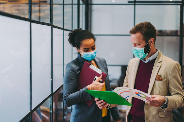 Business people talking while wearing masks in the office