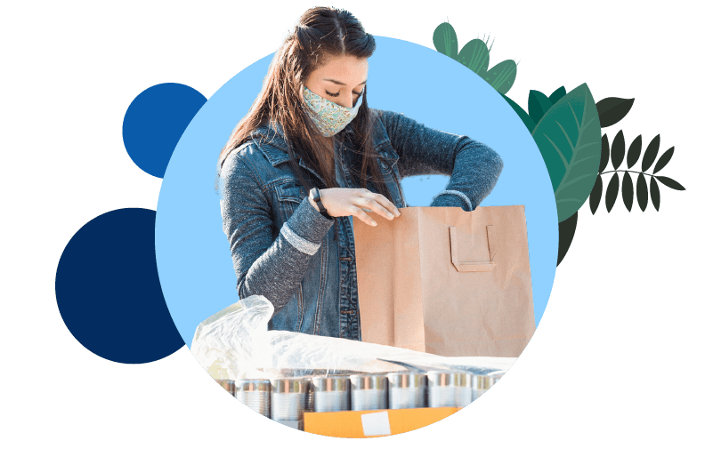 A woman wearing a mask while packing food into paper bags