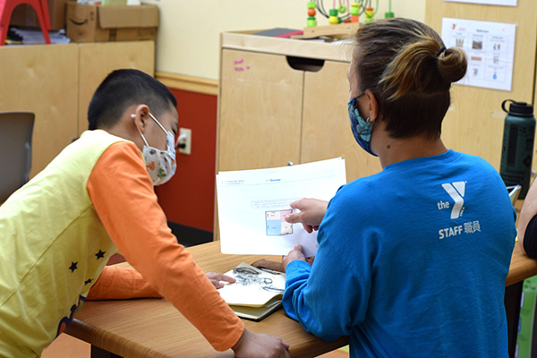 Kid and adult wearing masks while doing homework