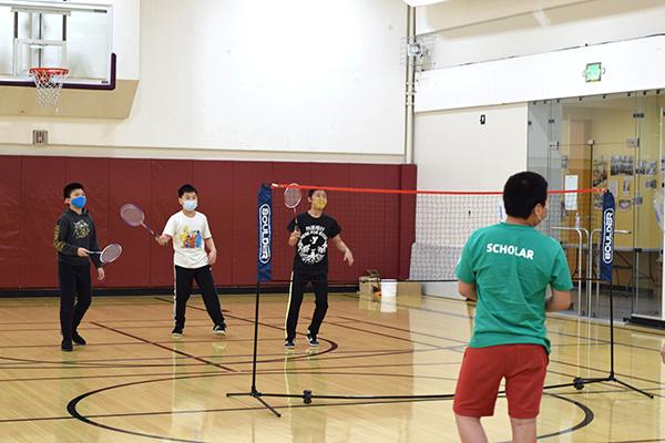 Kids playing badminton while wearing masks