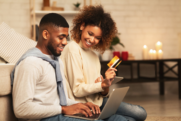 Two people submitting a payment on a computer