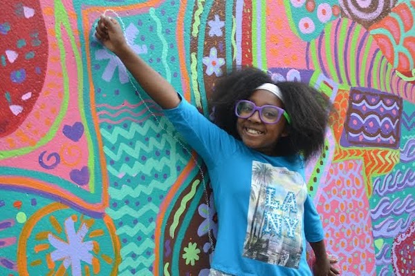 Girl smiling leaning against colorful wallr
