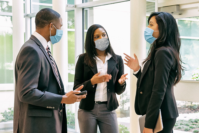 Employees having conversation while wearing masks