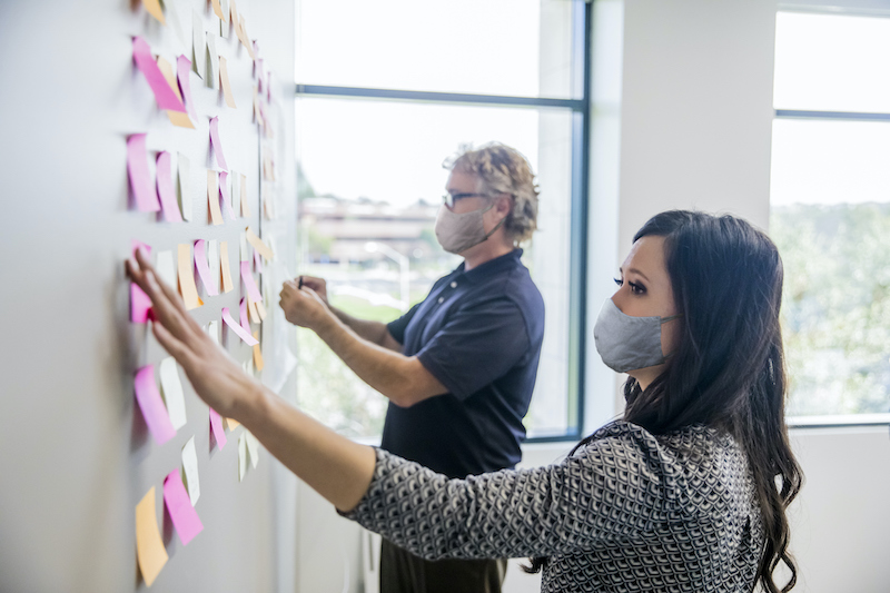 Two people leading a brainstorming session by putting post it notes on the wall