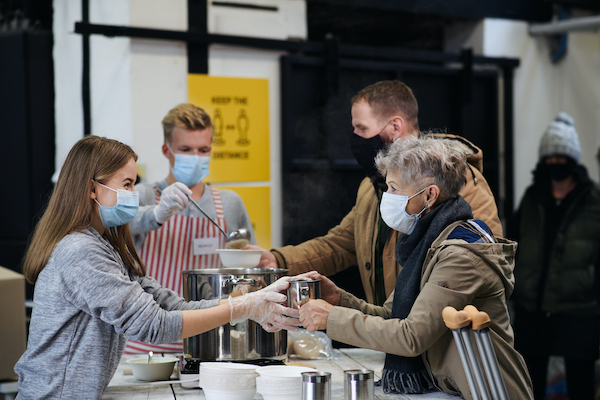 Volunteers wearing masks and serving hot soup at food bank