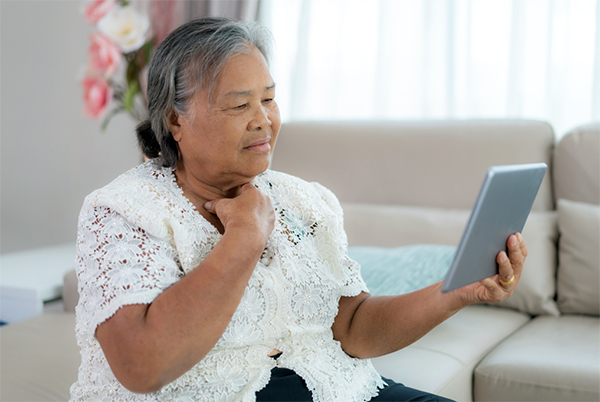 Older woman holds tablet at a distance to view