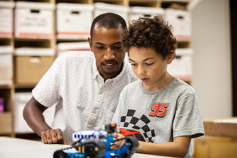 Child and mentor looking at robot car