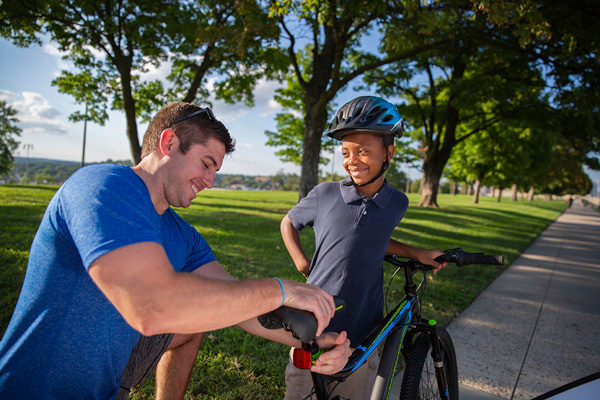 Young boy learning to ride a bike with mentor