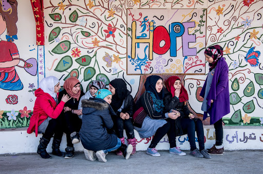 Young girls posing in front of mural