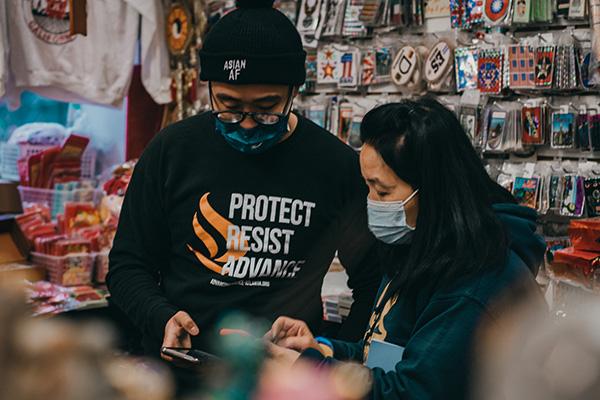 Man and woman looking at phones while wearing masks