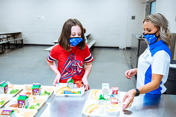 Woman serving lunch to children while wearing mask