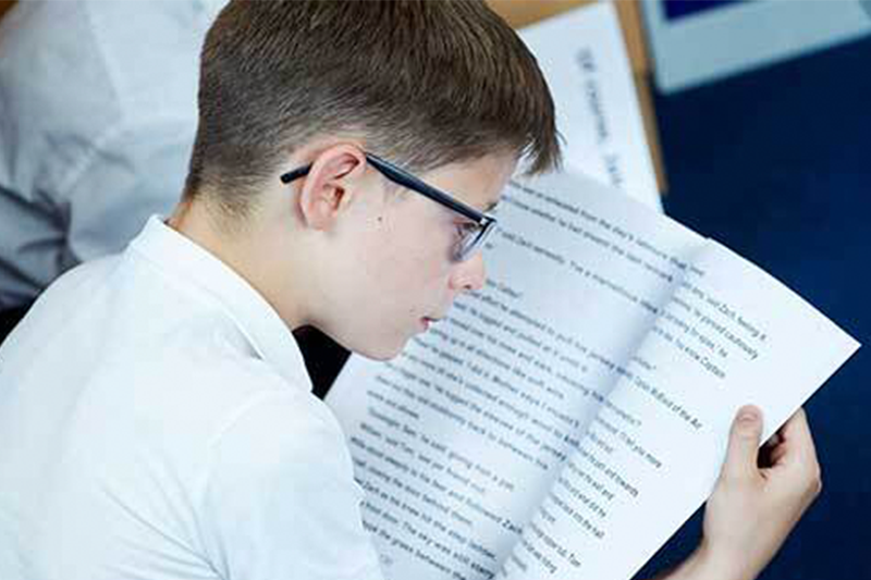 Boy wearing glasses reading book