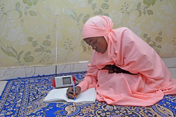 Young girl doing school work via radio