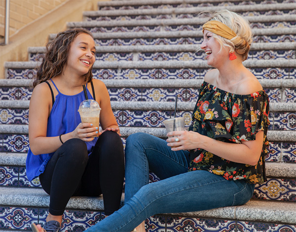 Woman and young adult sitting on steps laughing