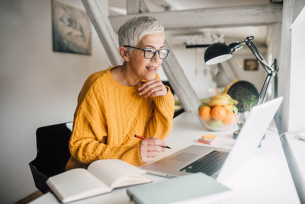 """Woman looking at computer"""" width=""""600"""" height=""""401"""" class="""