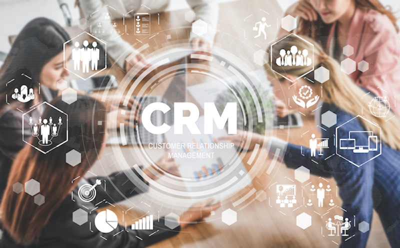 Image of people having a meeting with a CRM graphic overlaid