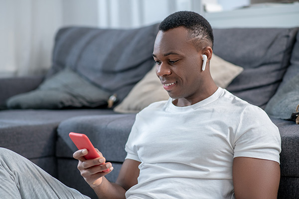 Man looking at phone with headphones in ears