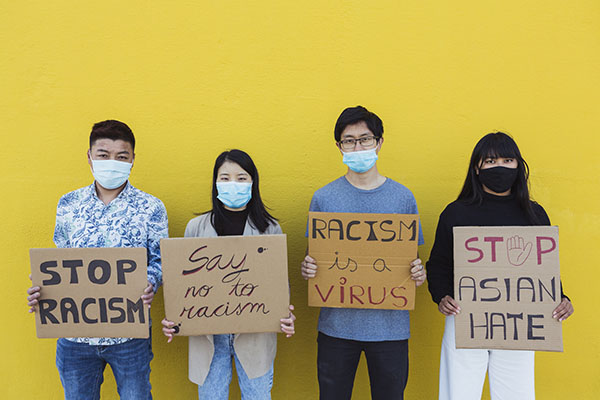 Young people holding up anti-racism signs in front of a yellow wall