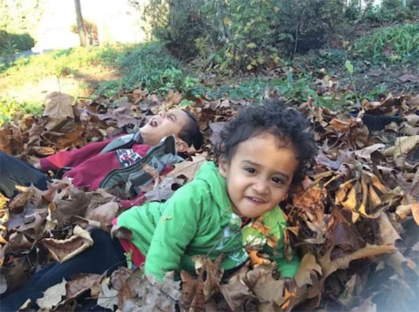 Boys rolling in leaves